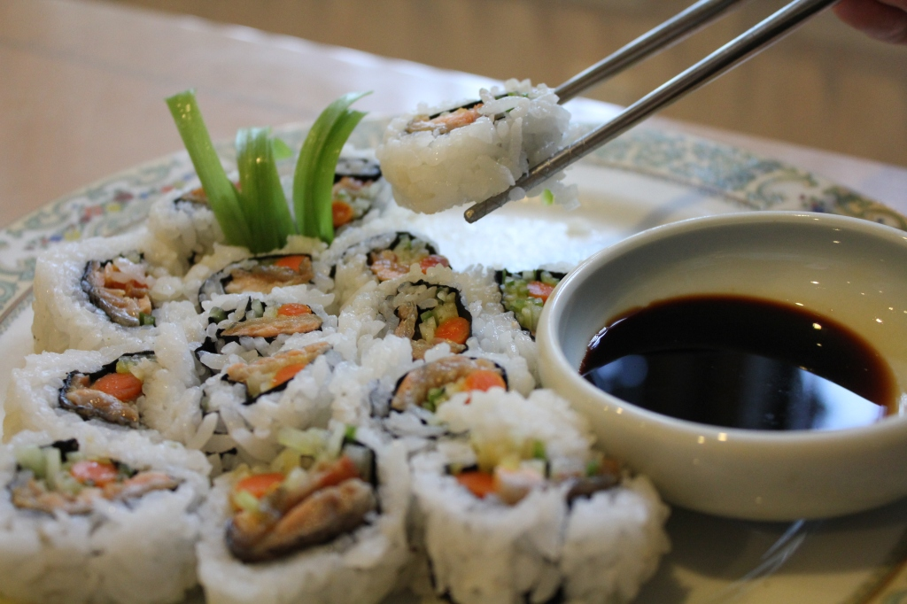 salmon skin roll dipping in soy sauce